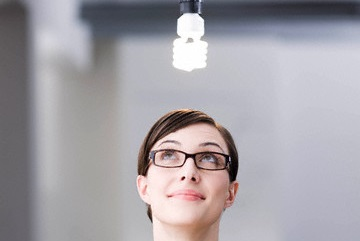Woman looking at a light bulb --- Image by © Emely/cultura/Corbis